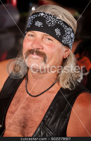 Grinning Tough Guy stock photo, Grinning middle aged man with leather vest and bandanna by Scott Griessel