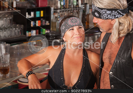 Tough Loving Couple in Bar stock photo, Mature biker gang female admiring man in bar by Scott Griessel