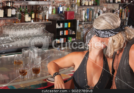 Kissing Biker Gang Couple stock photo, Pair of motorcycle gang lovers kissing at a bar by Scott Griessel