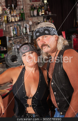 Attractive Biker Gang Couple stock photo, Attractive middle aged biker couple with bandannas in bar by Scott Griessel