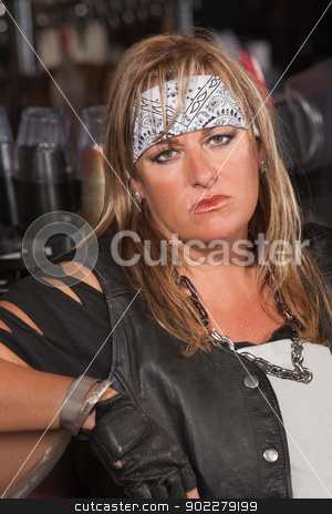 Serious Female Thug Leaning Back stock photo, Serious woman in motorcycle gang jacket leaning on counter by Scott Griessel