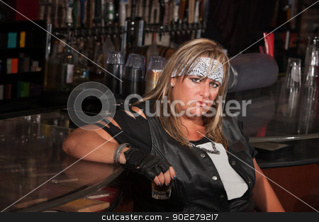 Grumpy Woman Holding Drink Glass stock photo, Grumpy biker gang lady holding her drink at a bar by Scott Griessel
