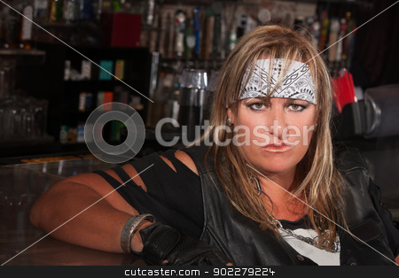 Woman in Bandanna at a Bar stock photo, Tough woman in bandanna and leather jacket sitting in a bar by Scott Griessel