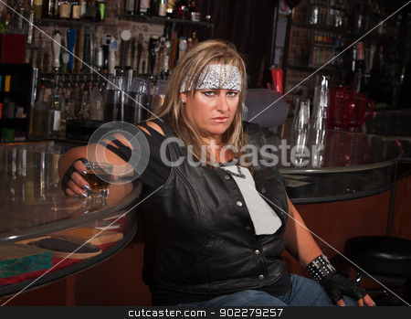 Angry Woman with Drink stock photo, Angry mature woman with alcohol leaning back in a tavern by Scott Griessel