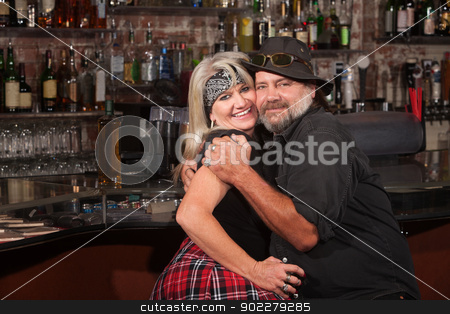 Happy Biker Couple Embracing stock photo, Happy middle aged couple embracing in a tavern by Scott Griessel