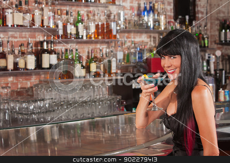 Pretty Smiling Woman with Martini stock photo, Cute smiling woman in black dress holding a blue martini by Scott Griessel