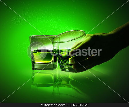 Two glasses of green absinth stock photo, Hand holding one of two glasses of green absinth by Sergey Nivens