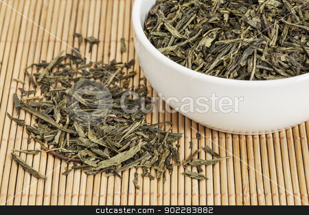 Sencha green tea stock photo, loose leaf Sencha green tea in a white china cup and spilled over bamboo mat by Marek Uliasz