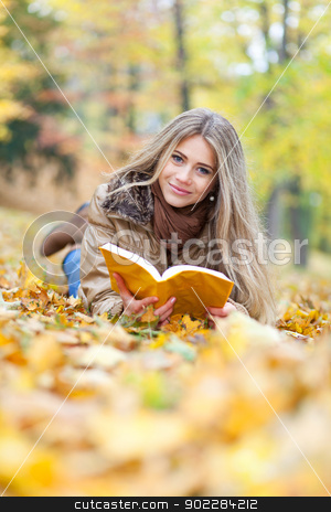 Young woman reading lying on leaves stock photo, Beautiful woman in a park, reading and smiling by tristanbm