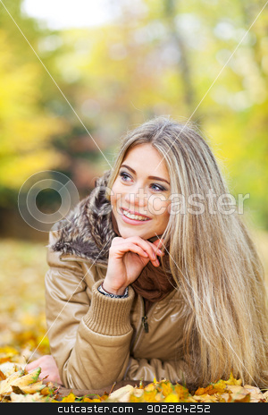 Relaxed woman in autumn stock photo, Pretty smiling girl lying in a park and looking something by tristanbm