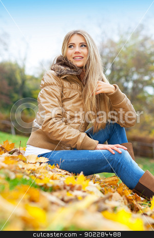 Blond woman sitting in a park stock photo, Young woman in a park in autumn by tristanbm