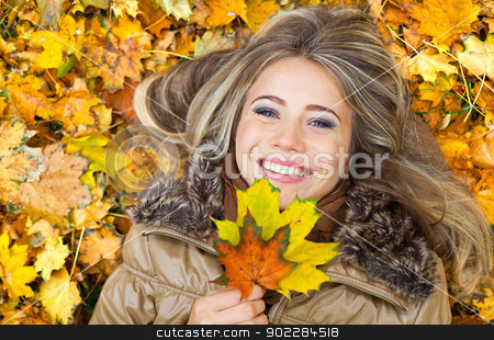 Smile in autumn leaves stock photo, Closeup portrait of a young woman surrounded by autumn leaves by tristanbm