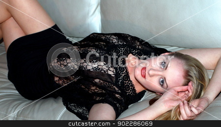 Sexy Blonde stock photo, Sexy blonde woman lying on a couch. by Henrik Lehnerer
