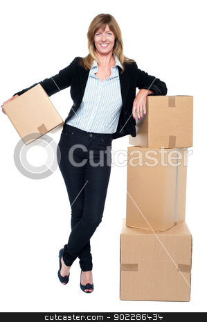 Business executive relocating her office space stock photo, Portrait of a business executive posing beside pile of cartons while holding one. by Ishay Botbol