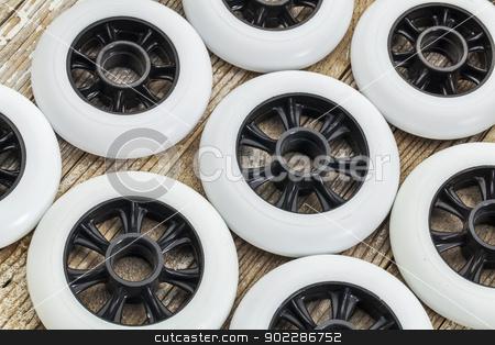 wheels for inline skating stock photo, white racing wheels for inline skating on wooden surface by Marek Uliasz
