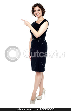Fashionable young lady indicating sideways stock photo, Full length shot of a fashionable woman pointing towards the copy space area. by Ishay Botbol