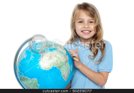 Young girl selecting holiday destination over globe stock photo, Attractive female child pointing out her holiday destination on the globe. by Ishay Botbol