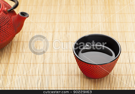 cup of tea with tetsubin stock photo, Japanese cup of tea with a tetsubin on a bamboo mat - a traditional cast iron red hobnail design with black enamel inside by Marek Uliasz