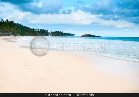 Tropical beach with cloudy dark blue sky  stock photo, Tropical beach with cloudy dark blue sky and footprint on yellow sand by Iryna Rasko