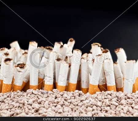 Wall of cigarettes stock photo, Ashtray full of smoked cigarettes in the sand disposed as wall of cigarettes  by Dario Rota
