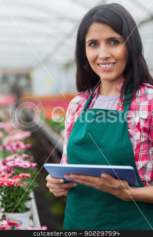 Woman doing inventory in greenhouse stock photo, Woman doing inventory with laptop in working in greenhouse by Wavebreak Media