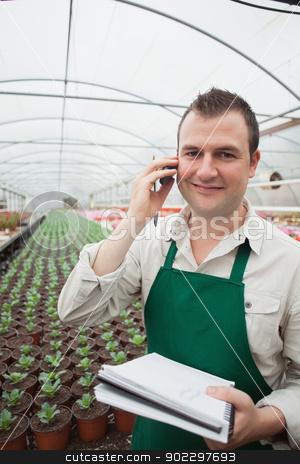 Worker taking notes and calling in greenhouse stock photo, Worker taking notes and calling in greenhouse nursery by Wavebreak Media