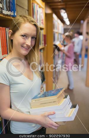 Student standing at a bookshelf  stock photo, Student standing at a bookshelf at the library by Wavebreak Media