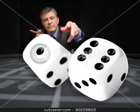 Gambler at the poker table with digital dice in foreground stock photo, Gambler at the poker table throwing digital dice in foreground by Wavebreak Media