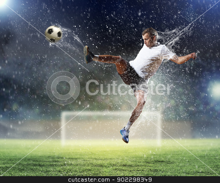 football player striking the ball stock photo, football player in white shirt striking the at the stadium under the rain by Sergey Nivens