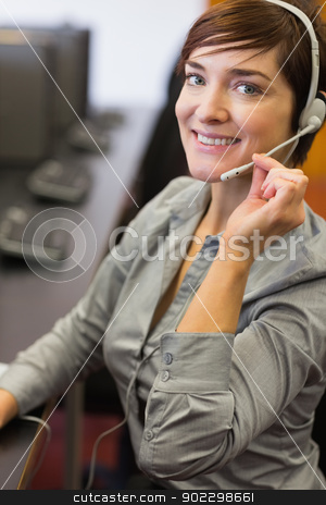Teacher sitting at the computer room wearing a headset stock photo, Teacher sitting at the computer room while wearing a headset in college by Wavebreak Media