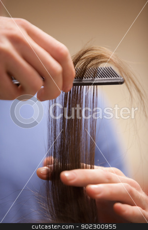 Close up of a hand combing hair stock photo, Close up of a hand combing hair with a comb by Wavebreak Media