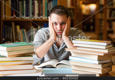 Depressed student having a lot to read stock photo, Depressed student having a lot to read looking at the camera by Wavebreak Media