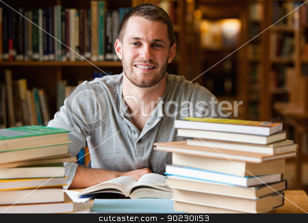 Smiling student surrounded by books stock photo, Smiling student surrounded by books in a library by Wavebreak Media