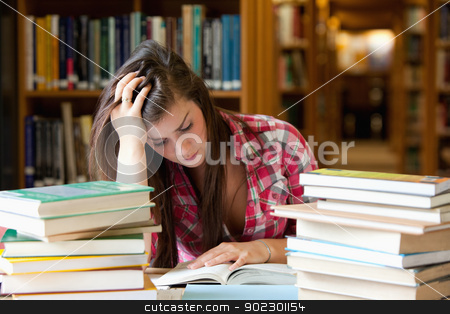 Focused student surrounded by books stock photo, Focused student surrounded by books in a library by Wavebreak Media