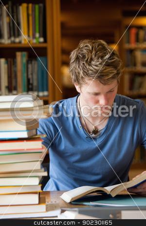 Portrait of a male student reading stock photo, Portrait of a male student reading in a library by Wavebreak Media