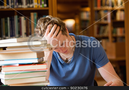 Studious man reading stock photo, Studious man reading in a library by Wavebreak Media