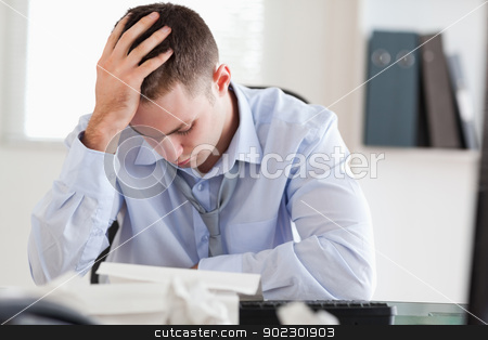 Businessman stressed while doing his accounting stock photo, Young businessman stressed while doing his accounting by Wavebreak Media