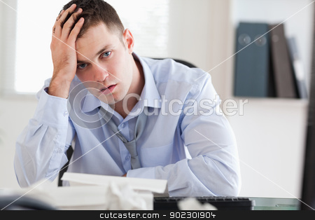 Businessman overextended with his accounting stock photo, Young businessman overextended with his accounting by Wavebreak Media