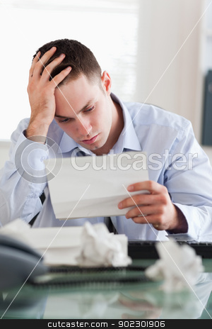 Businessman reading a bill stock photo, Frustrated businessman reading a bill by Wavebreak Media