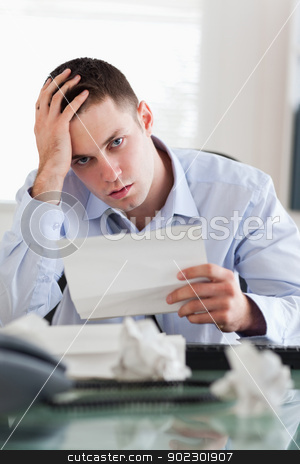 Close up of businessman worried about bills stock photo, Close up of young businessman worried about bills by Wavebreak Media