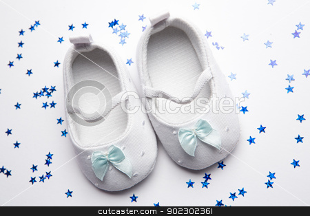 Baby blue booties with confetti stock photo, Baby blue booties with confetti on white background by Wavebreak Media