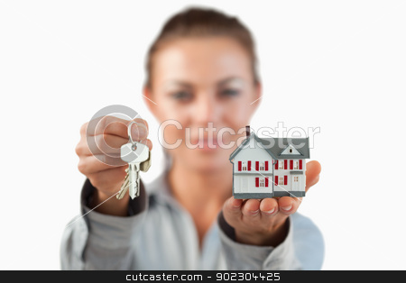 Miniature house and keys being presented by female estate agent stock photo, Miniature house and keys being presented by female estate agent against a white background by Wavebreak Media