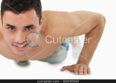Young male doing push ups stock photo, Young male doing push ups against a white background by Wavebreak Media