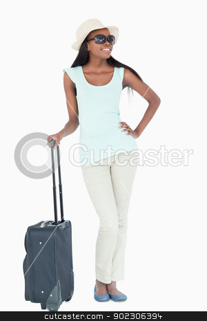 Happy smiling young woman with her suitcase stock photo, Happy smiling young woman with her suitcase against a white background by Wavebreak Media