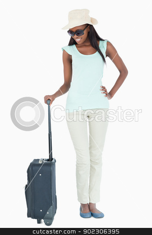 Smiling young woman looking at her suitcase stock photo, Smiling young woman looking at her suitcase against a white background by Wavebreak Media
