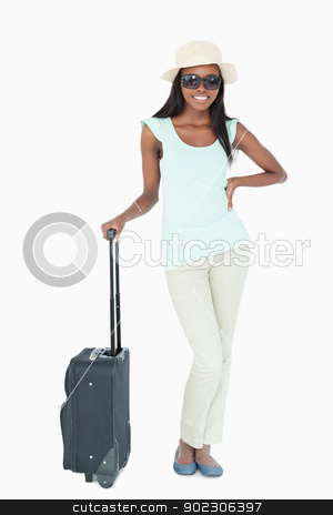 Smiling young woman with suitcase stock photo, Smiling young woman with suitcase against a white background by Wavebreak Media
