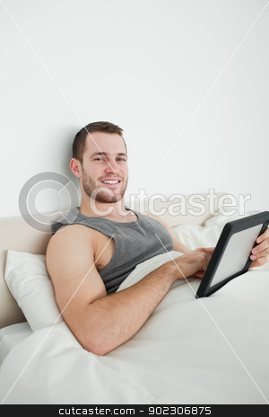 Portrait of a young man using a tablet computer stock photo, Portrait of a young man using a tablet computer in his bedroom by Wavebreak Media