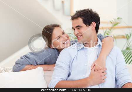 Smiling couple hugging stock photo, Smiling couple hugging in their living room by Wavebreak Media