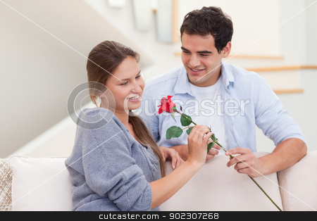 Man offering a rose to his fiance stock photo, Man offering a rose to his fiance in their living room by Wavebreak Media