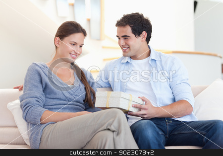 Man offering a gift to his girlfriend stock photo, Man offering a gift to his girlfriend in their living room by Wavebreak Media